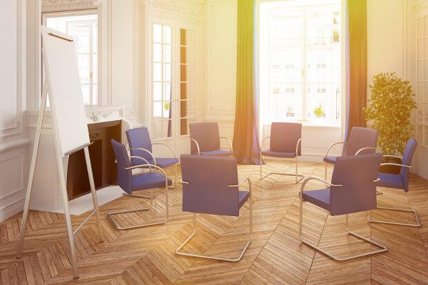 Heller Tagungsraum mit Stuhlkreis und Flipchart